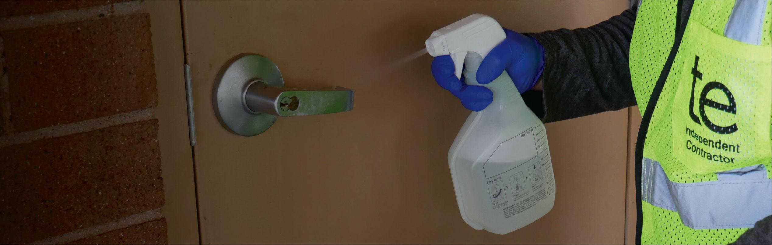 TaskEasy contractor sanitizing a door knob